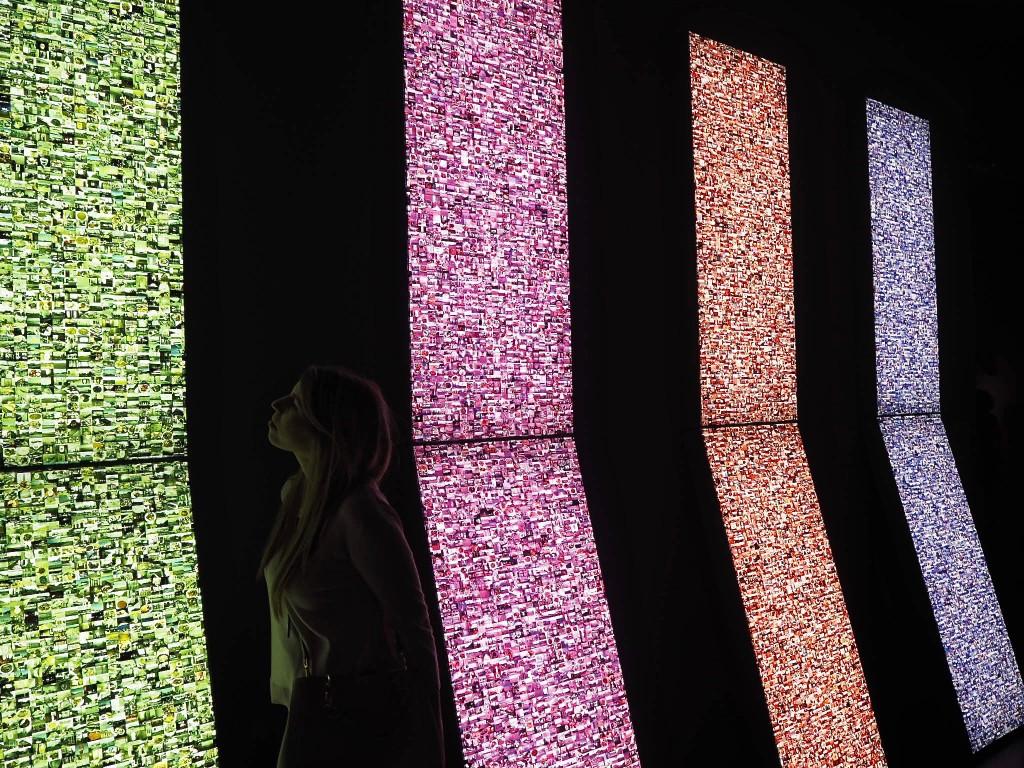 Bunte Lichtsäulen mit tausenden Bildern eines Künstlers.