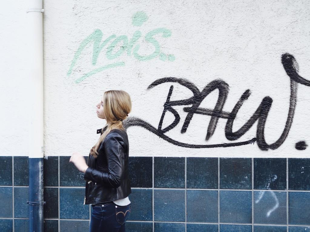 Junge Frau beim Spaziergang durch die Stadt mit Graffiti im Hintergrund.