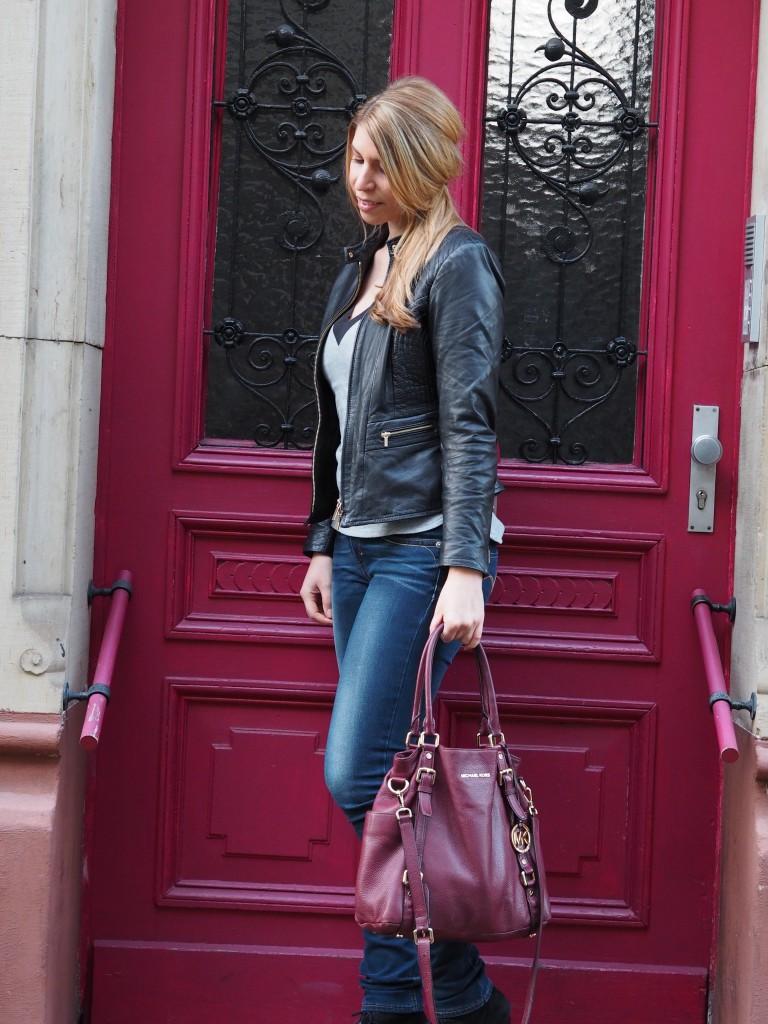 Outfitpost: Julie trägt eine Jeans, Lederjacke und ein cooles Shirt. Im Arm hält sie eine bourdeauxfarbene Michael Kors-Tasche.