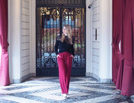 Die schicke Modebloggerin Julie en Rose ist aus der Babypause zurück. Sie trägt eine moderne, rote Hose, edle Pumps in Gold und einen schwarzen Pullover mit transparenten Einsätzen.